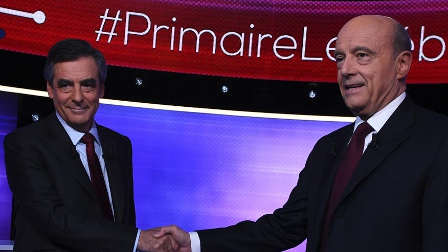 The two finalists for the right-wing Les Republicains (LR) party primaries ahead of the 2017 presidential election, Francois Fillon, left, and Alain Juppe, shake hands before taking part of a TV debate at French TV station TF1, in Boulogne-Billancourt, outside Paris Thursday Nov. 24, 2016. Former Prime Ministers Francois Fillon and Alain Juppe will meet in a runoff next Sunday for the nomination to be France's conservative candidate for president. (Eric Feferberg/ Pool Photo via AP)