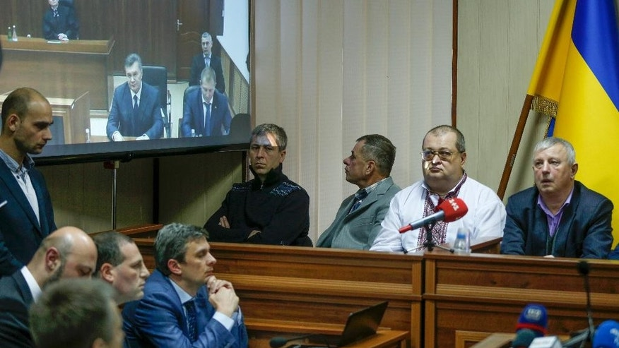 Ukraine's ousted president Viktor Yanukovych, left on the screen, speaks via video link from Russian city Rostov-on-Don, in a court room in Kiev, Ukraine, Friday, Nov. 25, 2016. Video testimony by Ukraine's ousted president has been postponed in the trial of five former special forces policemen charged with fatally shooting scores of demonstrators. (AP Photo/Sergei Chuzavkov)