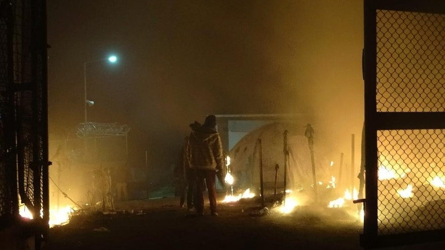 Refugees stand next to the burning tents at the Moria refugee camp on the northeastern Greek island of Lesbos, early Friday, Nov. 25, 2016. Police say two people have died on the Greek island of Lesbos and two others were seriously injured after a fire raged through a refugee camp used for migrants facing deportation back to Turkey. (AP Photo)