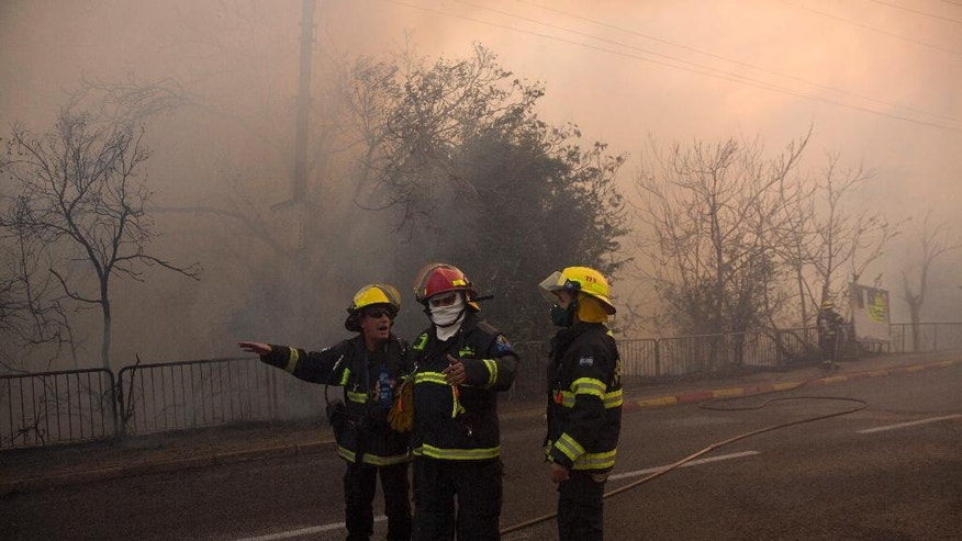 Firefighters work at the site  ofwildfires in Haifa, Israel, Thursday, Nov. 24, 2016. The blaze ripped through parts of Israel's third-largest city, forcing tens of thousands of people to evacuate their homes and prompting a rare call-up of hundreds of military reservists to join overstretched police and firefighters. Spreading quickly due to dry, windy weather, the fire quickly spread through Haifa's northern neighborhoods. While there were no serious injuries, several dozen people were hospitalized for smoke inhalation. (AP Photo/Ariel Schalit)