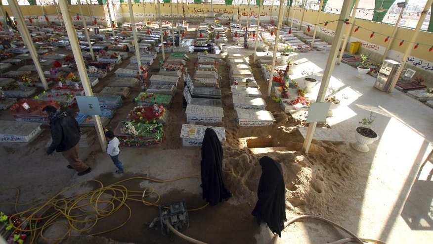 """Women pray by the graves of militiamen killed from fighting with Islamic State group militants at the Wadi al-Salam, or """"Valley of Peace"""" cemetery in Najaf, 100 miles (160 kilometers) south of Baghdad, Iraq on Friday, Nov. 25, 2016. For decades, the rapid expansion of the cemetery in Iraq's holy Shiite city of Najaf has testified to the scale of violence of Iraq's contemporary history, from the ruinous 1980-88 war with Iran to the costly 1990-91 conflict over Kuwait and 13 years of uninterrupted bloodshed starting with the U.S. led invasion in 2003. With the government not publicizing casualties among the Shiite-dominated security forces now fighting in Mosul, burials in the sprawling cemetery offers a reliable indicator of battlefield losses on the government side. (AP Photo)"""