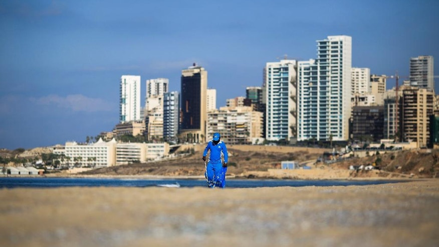 In this Tuesday, Nov. 15, 2016 photo, a waste management worker cleans Beirut's Ramlet al-Baida shore, Lebanon. Ramlet al-Baida is an outlet for locals and foreigners who can't pay for Lebanon's expensive private beaches. But a new luxury development project is set to turn its southern corner into another exclusive alcove. (AP Photo/Hassan Ammar)