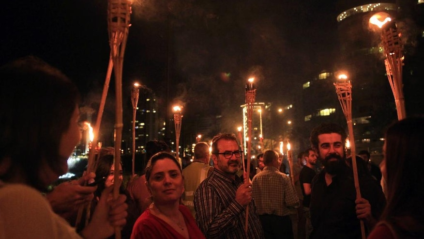 In this Tuesday, Nov. 15, 2016 photo, activists hold torches at a demonstration against the Eden Rock Resort development on Beirut's Ramlet al-Baida shore, Lebanon. Ramlet al-Baida is an outlet for locals and foreigners who can't pay for Lebanon's expensive private beaches. But a new luxury development project is set to turn its southern corner into another exclusive alcove. (AP Photo/Bilal Hussein)