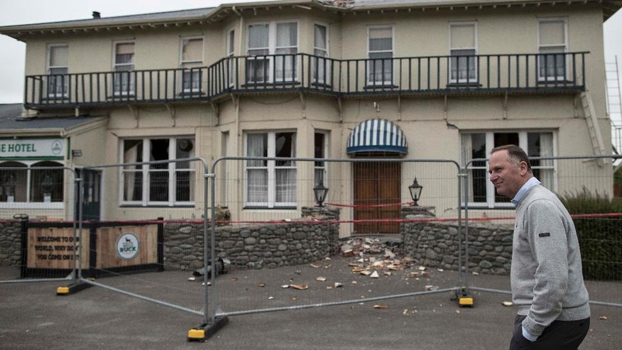 In this Thursday Nov. 24, 2016 photo, New Zealand Prime Minister John Key inspects damage to the Waiau Lodge Hotel in Waiau, New Zealand, after a magnitude 7.8 earthquake hit the region 10 days earlier. In terms of human life, the magnitude 7.8 earthquake that hit New Zealand this month was relatively merciful: just two fatalities. But geologically, it moved roads and mountains and even displaced the sea, leaving a formidable mark from which tourism, farming and life in general may need years to recover. (Iain McGregor/Pool Photo via AP)