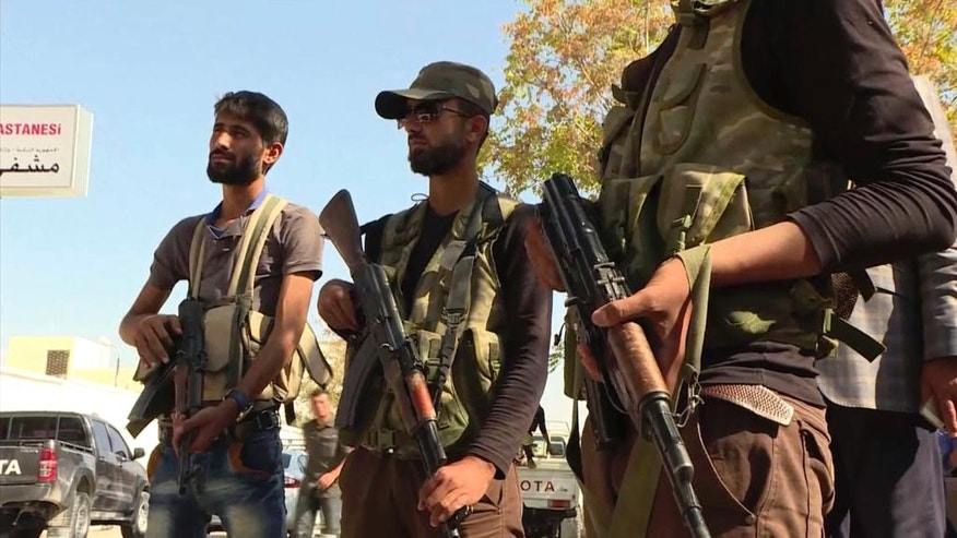 FILE - In this Sunday, Oct. 16, 2016 file image made from video posted online by Qasioun News Agency, Turkish-backed Syrian opposition forces patrol in Dabiq, Syria. Turkey is pushing ahead with plans to liberate the town of al-Bab, the last major Islamic State stronghold in northern Syria despite a complicated terrain. (Qasioun News Agency via AP, File)