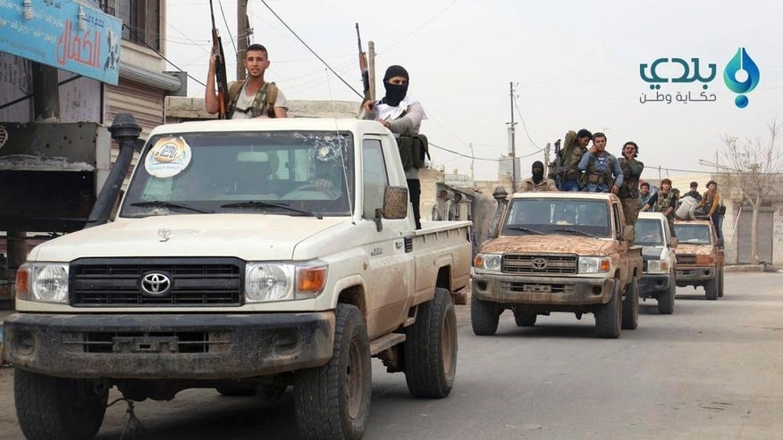 This photo released on Sunday, Nov. 13, 2016 by the Baladi News Network, an opposition activist media organization, which has been authenticated based on its contents and other AP reporting, shows Turkey-backed Syrian opposition fighters raising their guns in the back of pick-up trucks in northern Syria. Turkey is pushing ahead with plans to liberate the town of al-Bab, the last major Islamic State stronghold in northern Syria despite a complicated terrain. (Baladi News Network via AP)