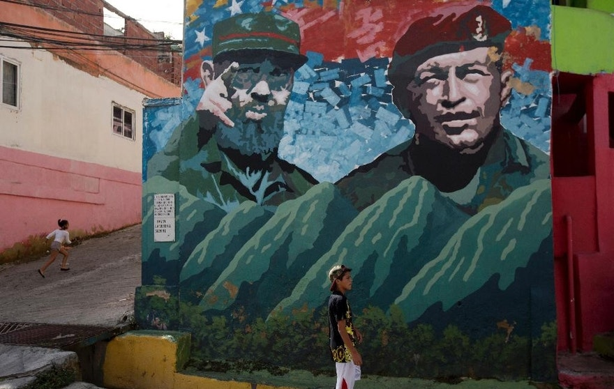 "Boys play near a graffiti of Fidel Castro, left, and late President of Venezuela Hugo Chavez at ""23 de Enero"" neighborhood in Caracas, Venezuela, Saturday, Nov. 26, 2016. Castro, who led a rebel army to improbable victory, embraced Soviet-style communism and defied the power of 10 U.S. presidents during his half century rule of Cuba, died at age 90. (AP Photo/Fernando Llano)"