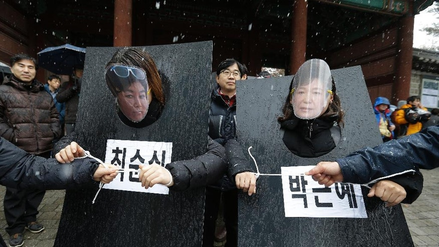 South Korean protesters wearing masks of South Korean President Park Geun-hye, right, and Choi Soon-sil, Park's longtime friend, march with their hands tied by ropes on black boards bearing their names during a rally calling for Park to step down in Seoul, South Korea, Saturday, Nov. 26, 2016. For the fifth straight weekend, masses of protesters occupied major avenues in downtown Seoul on Saturday, demanding the ouster of Park who is suspected of helping in the criminal activities of a secretive confidante who is accused of manipulating government affairs and extorting companies to build an illicit fortune. (AP Photo/Ahn Young-joon)