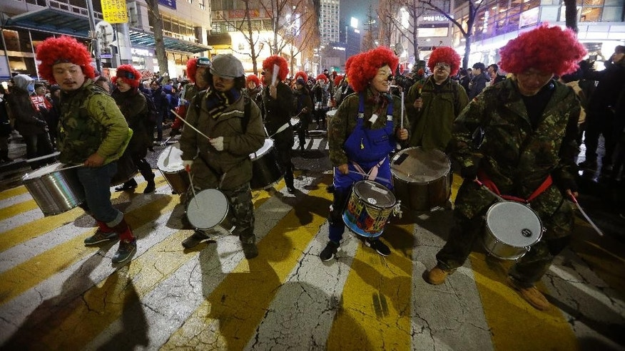 South Korean protesters beat their drums as they march during a rally calling for South Korean President Park Geun-hye to step down in Seoul, South Korea, Saturday, Nov. 26, 2016. For the fifth-straight weekend, masses of protesters are expected to occupy major avenues in downtown Seoul on Saturday demanding the ouster of Park, who  is suspected of helping in the criminal activities of a secretive confidante who is accused of manipulating government affairs and extorting companies to build an illicit fortune. (AP Photo/Ahn Young-joon. Pool)