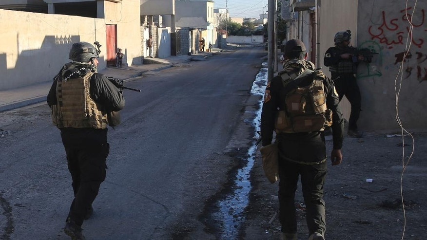 Iraqi special forces soldiers patrol in the Bakr front line neighborhood, in Mosul, Iraq, Friday Nov. 25, 2016. Iraqi special forces fought house to house in Mosul, while focusing efforts on winning hearts and minds among civilians and gleaning information about Islamic State militants holed up in buildings sometimes just a block away. (AP Photo/Hussein Malla)