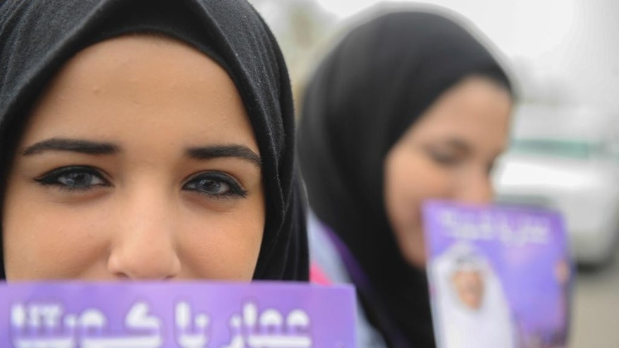 Kuwaiti girls hold up candidate cards as they head to the polls to choose parliamentary representatives, in Kuwait City, Saturday, Nov.26, 2016.  Kuwaitis voted Saturday for representatives in the tiny, oil-rich country's parliament Saturday as the Gulf nation struggles to cope with a slump in oil prices that is straining public finances. (AP Photo/Jabber Abdulkhaleg)