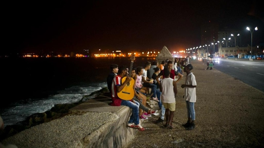 People gather at as usual at the Malecon after President Raul Castro announced the death of his brother Fidel on national TV in Havana, Cuba, early Saturday Nov. 26, 2016. Former President Fidel Castro, who led a rebel army to improbable victory in Cuba, embraced Soviet-style communism and defied the power of 10 U.S. presidents during his half century rule, has died at age 90. (AP Photo/Ramon Espinosa)