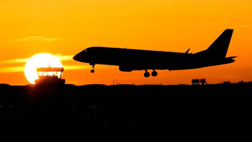 A plane lands during sunrise at the airport in Duesseldorf, Germany, Friday, Nov. 25,  2016.  Lufthansa pilots will continue their strike at least until Saturday. (Marcel Kusch/dpa via AP)