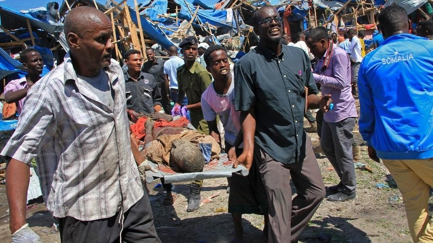 Somali men retrieve the dead body of a person who was killed when a car bomb targeted a police station in the Waberi neighborhood, where President Hassan Sheikh Mohamud was visiting a university, in the capital Mogadishu,  Saturday, Nov. 26, 2016. A Somali police official says a car bomb has exploded near a police station in a busy market in the Somali capital, killing a number of people and wounding others. (AP Photo/Farah Abdi Warsameh)