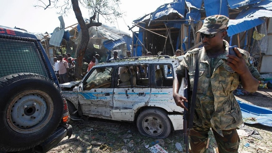 A soldier stands near the wreckage after a car bomb that targeted a police station in the Waberi neighborhood, where President Hassan Sheikh Mohamud was visiting a university, in the capital Mogadishu, Somalia Saturday, Nov. 26, 2016. A Somali police official says a car bomb has exploded near a police station in a busy market in the Somali capital, killing a number of people and wounding others. (AP Photo/Farah Abdi Warsameh)