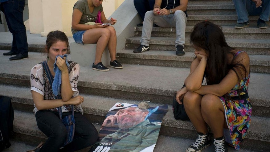 Young women join a gathering one day after the death of Fidel Castro in Havana, Cuba, Saturday, Nov. 26, 2016. Cuba will observe nine days of mourning for the former president who ruled Cuba for half a century. (AP Photo/Ramon Espinosa)
