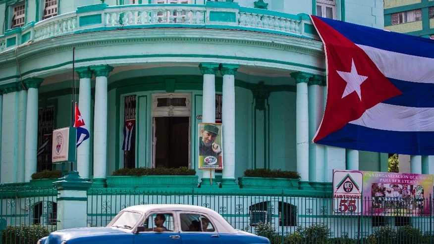 A Cuban flag flies at half-mast, left, and a picture of Fidel Castro decorates the headquarters of the Committees for the Defense of the Revolution (CDR), one day after Castro died in Havana, Cuba, Saturday, Nov. 26, 2016. Castro, who led a rebel army to improbable victory in Cuba, embraced Soviet-style communism and defied the power of U.S. presidents during his half century rule, died at age 90 late Friday, Nov. 25. (AP Photo/Desmond Boylan)