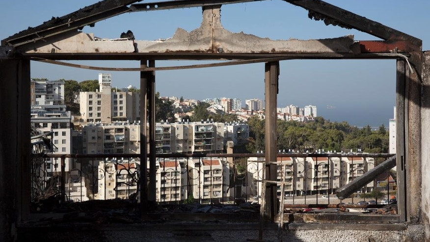 The Mediterranean sea and parts of the city can bee sen through a burned house following wildfires in Haifa, Israel, Friday, Nov. 25, 2016. Israeli firefighters reined in a blaze that had spread across the country's third-largest city and forced tens of thousands of people to flee their homes, but continued to battle more than a dozen other fires around the country for the fourth day in a row. (AP Photo/Ariel Schalit)
