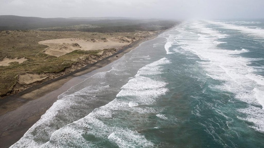 Muriwai beach is seen Sunday, Nov. 27, 2016 after the chartered fishing boat Francie disappeared off Auckland, New Zealand. The Francie carrying 11 people disappeared from view in large waves on Saturday at the entrance to Kaipara Harbour near Auckland. (Greg Bowker/New Zealand Herald via AP)