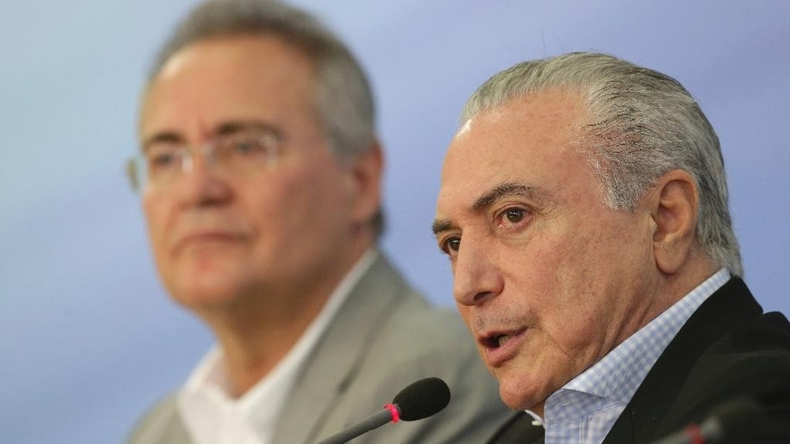 Brazil's President Michel Temer speaks to the press about proposed anti-corruption legislation, flanked by Federal Senate President Renan Calheiros in Brasilia, Brazil, Sunday, Nov. 27, 2016. Many Brazilians are concerned the legislation to toughen prosecution of corruption might perversely offer amnesty to politicians who had previously engaged in the practice. (AP Photo/Eraldo Peres)