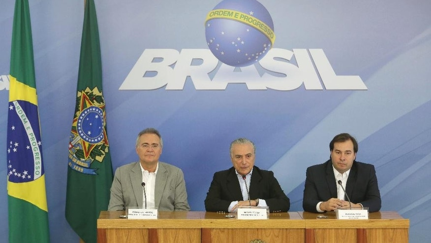 Brazil's President Michel Temer, center, speaks to the press about proposed anti-corruption legislation, flanked by Federal Senate President Renan Calheiros, left, and Chamber of Deputies President Rodrigo Maia, in Brasilia, Brazil, Sunday, Nov. 27, 2016. Many Brazilians are concerned the legislation to toughen prosecution of corruption might perversely offer amnesty to politicians who had previously engaged in the practice. (AP Photo/Eraldo Peres)