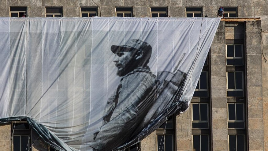 Men hang a giant banner with a picture of Cuba's late leader Fidel Castro as a young revolutionary, from the Cuban National Library building in Havana, Cuba, Sunday, Nov. 27, 2016. Cuba's government declared nine days of national mourning after Castro died Friday and this normally vibrant city has been notably subdued. (AP Photo/Desmond Boylan)