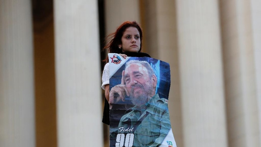 A student stands at attention holding images of Fidel Castro at the university where Castro studied law as a young man, during a vigil in Havana, Cuba, Sunday, Nov. 27, 2016. Castro, who led a rebel army to improbable victory in Cuba, embraced Soviet-style communism and defied the power of U.S. presidents during his half century rule, died Friday at age 90. (AP Photo/ Dario Lopez-Mills)