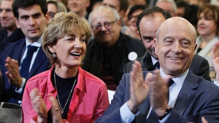 Alain Juppe, a candidate in Sunday's primary runoff to select a conservative candidate for the French presidential election, and his wife Isabelle applaud during a meeting in Nancy, eastern France, Friday, Nov. 25, 2016. Francois Fillon, a champion of free-market economics and traditional family values must defeat Juppe a moderate who accuses his rival of pandering to the far right. (AP Photo/Mathieu Cugnot)
