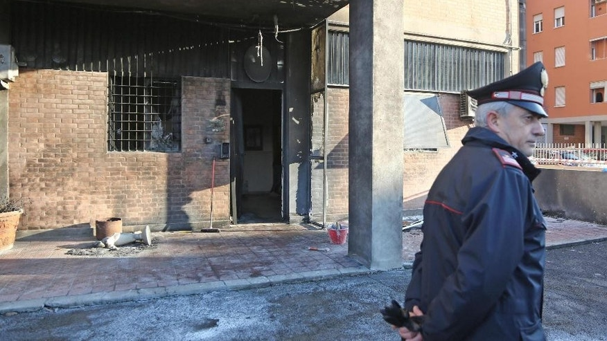 An Italian Carabinieri paramilitary police officer stands outside a Carabinieri station damaged by an explosion, caused by two canisters of gasoline ignited by a fuse in Bologna, Italy, Sunday Nov. 27, 2016. Italian authorities are investigating the overnight explosion that damaged the building but caused no injuries.  (Giorgio Benevenuti/ANSA via AP)