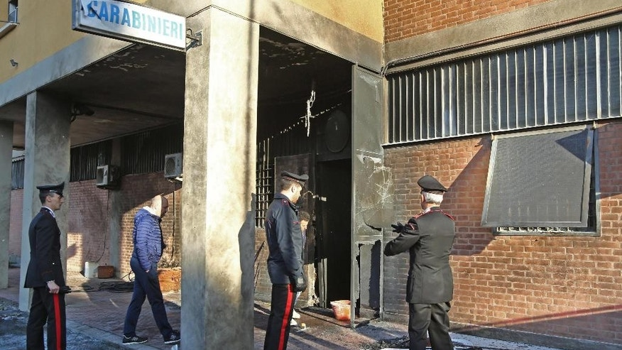 Italian Carabinieri paramilitary police officers stand outside a Carabinieri station damaged by an explosion, caused by two canisters of gasoline ignited by a fuse in Bologna, Italy, Sunday Nov. 27, 2016. Italian authorities are investigating the overnight explosion that damaged the building but caused no injuries.  (Giorgio Benevenuti/ANSA via AP)