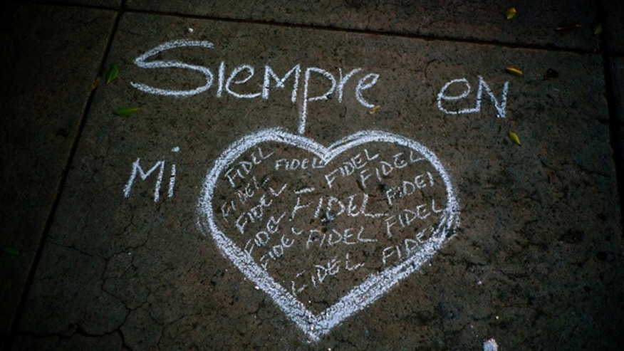 "A heart and the text that reads in Spanish ""Always in my heart Fidel"" are outlined in chalk on a sidewalk, during a vigil at the university where the late Cuban leader Fidel Castro studied law as a young man in Havana, Cuba, Saturday, Nov. 26, 2016. Castro, who led a rebel army to improbable victory in Cuba, embraced Soviet-style communism and defied the power of U.S. presidents during his half century rule, died at age 90. (AP Photo/Ramon Espinosa)"