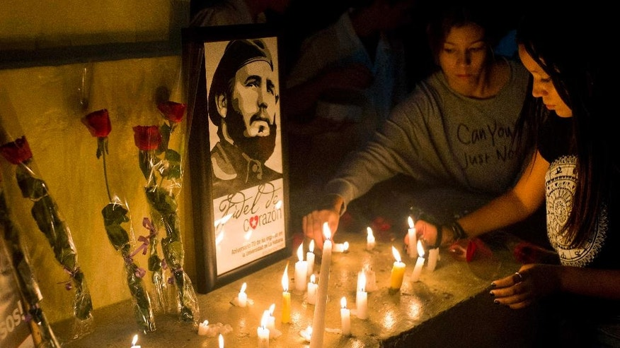 Students place candles around an image of the late Cuban leader Fidel Castro, at the university where Castro studied law as a young man, during a vigil in Havana, Cuba, Saturday, Nov. 26, 2016. Castro, who led a rebel army to improbable victory in Cuba, embraced Soviet-style communism and defied the power of U.S. presidents during his half century rule, died at age 90. (AP Photo/Ramon Espinosa)