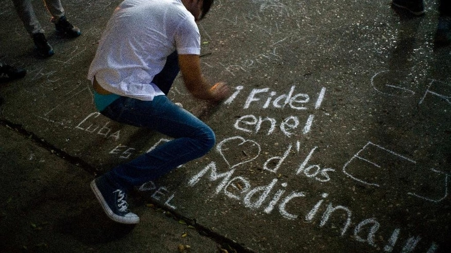 "A student writes on a sidewalk with chalk ""Fidel in the hearts of the med students"" during a vigil for the late Cuban leader Fidel Castro at the university where Castro studied law as a young man in Havana, Cuba, Saturday, Nov. 26, 2016. Castro, who led a rebel army to improbable victory in Cuba, embraced Soviet-style communism and defied the power of U.S. presidents during his half century rule, died at age 90. (AP Photo/Ramon Espinosa)"