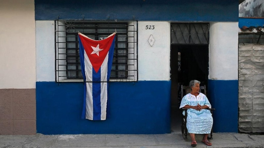 A woman sits in the doorway of her home, decorated with a Cuban flag in honor of the late Fidel Castro in the town of Regla on the outskirts of Havana, Cuba, Sunday, Nov. 27, 2016. Cuba will observe nine days of mourning for the former president who ruled Cuba for half a century.  (AP Photo/Enric Marti)