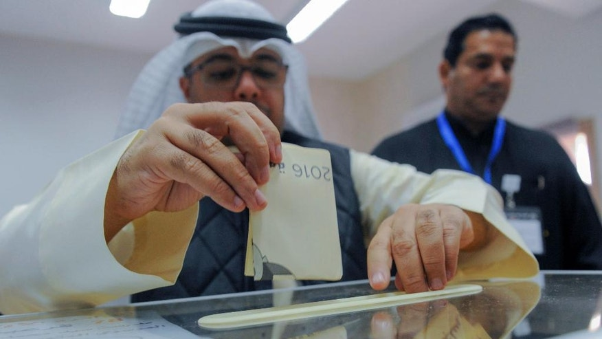 A Kuwaiti man casts his ballot to choose parliamentary representatives, in Kuwait City, Saturday, Nov.26, 2016. Kuwaitis voted Saturday for representatives in the tiny, oil-rich country's parliament Saturday as the Gulf nation struggles to cope with a slump in oil prices that is straining public finances. (AP Photo/Jabber Abdulkhaleg)