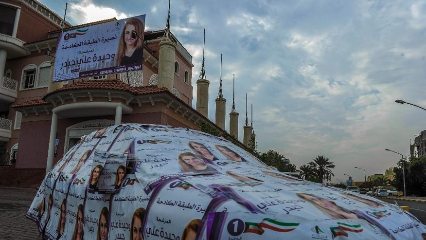 A car is covered in an election candidate's poster, in Kuwait City, Saturday, Nov.26, 2016.  Kuwaitis voted Saturday for representatives in the tiny, oil-rich country's parliament Saturday as the Gulf nation struggles to cope with a slump in oil prices that is straining public finances. (AP Photo/Jabber Abdulkhaleg)