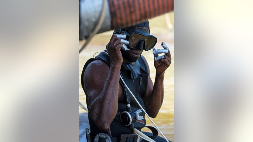 In this Oct. 30, 2016 photo, a gold miner from the Paamaka tribe known as Luck, prepares to dive to the bottom of the Marowijne river near the town of Langa Tabiki. The diver has to direct the large hose that is used to suck up mud and gold from the river bottom. The mud consequently goes through an industrial sieve and is mixed with mercury to extract gold from it. (AP Photo/Pieter Van Maele)