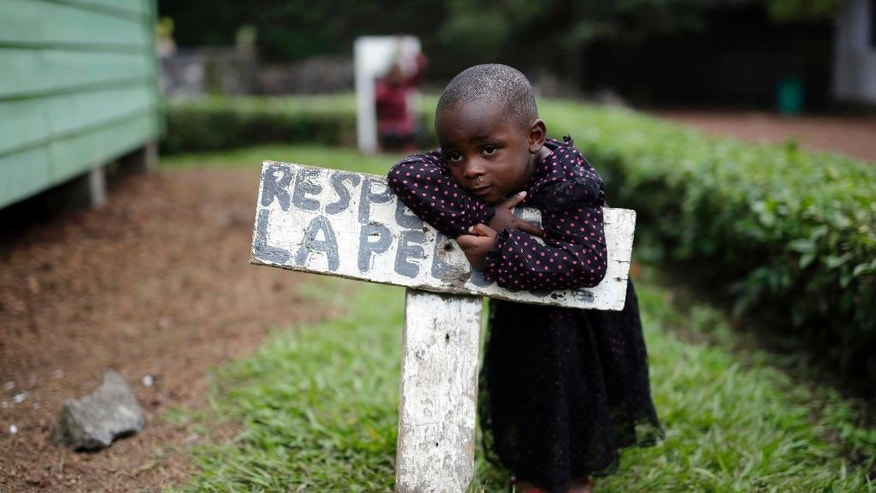 "In this photo taken on Monday, June 20, 2016, Rachel Wanimigabo, three, rests on a sign reading ""respect the grass"" at the En Avant Les Enfants INUKA center in Goma, Democratic Republic of Congo. Rachel's mother died giving birth to her youngest brother in April 2016. Her father disappeared. (AP Photo/Jerome Delay)"