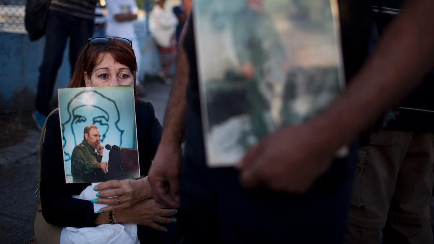 A woman holds an image of the late Fidel Castro as she waits in line to pay her final respects to the late leader, in Havana, Cuba, Monday, Nov. 28, 2016. Thousands of Cubans began lining up early for the start of week-long services bidding farewell to the man who ruled the country for nearly half a century. Cuba's government has declared nine days of national mourning following Castro's death Friday night at age 90. (AP Photo/Rodrigo Abd)