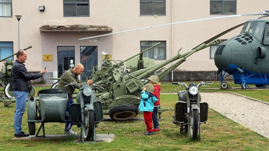 Children pose for photogrpahs near old outdated weaponry of the Albanian army which are on show at the Defense Ministry in the capital Tirana, Monday Nov. 28, 2016, for the celebrations of Independence Day. Albania joined NATO in 2009, and since then has been replacing outdated weaponry with the new ones in line with the alliance's standards. (AP Photo Hektor Pustina)