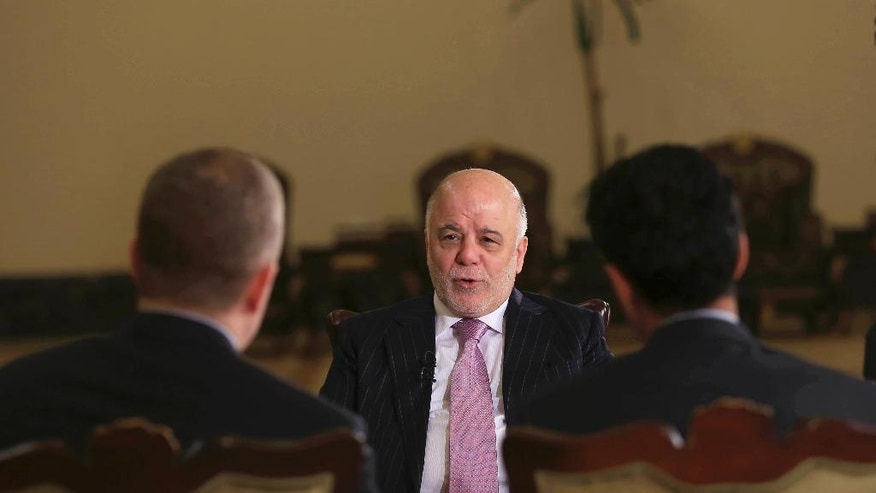"Iraq's Prime Minister Haider al-Abadi, center, speaks during an interview with the Associated Press in Baghdad, Iraq, Monday, Nov. 28, 2016. Al-Abadi said Islamic State fighters lack the ""gut"" to withstand a long battle with his forces for the city of Mosul, which he says may be back in Iraqi hands by the end of 2016. In a wide-ranging interview with The Associated Press in Baghdad, al-Abadi said Mosul was now completely encircled and that the speed in which the surrounding area had been secured had surpassed his expectations. (AP Photo/Khalid Mohammed)"