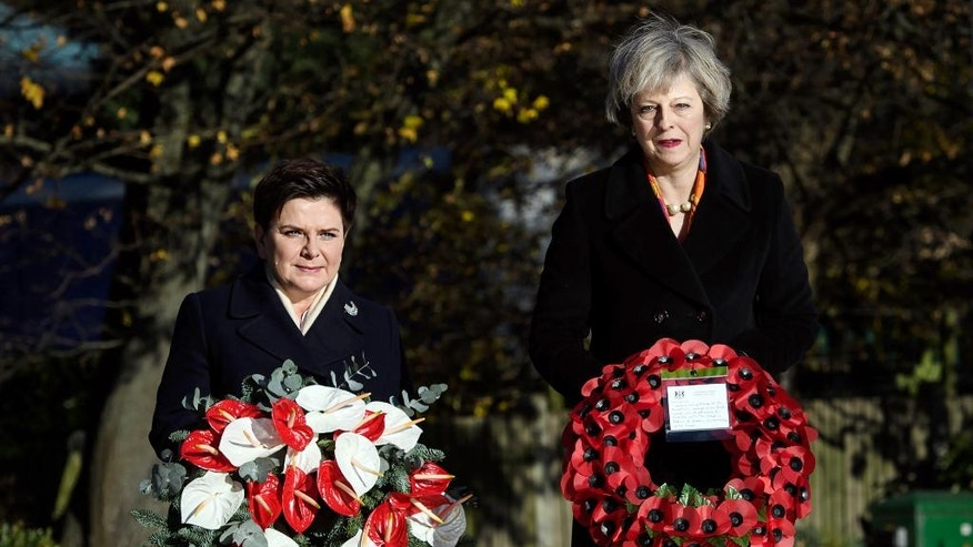 Britain's Prime Minister Theresa May, right, and Poland's Prime Minister Beata Szydlo lay wreaths at the Polish War Memorial in Northolt, London, ahead of the UK-Poland Inter-Governmental Consultations, Monday Nov. 28, 2016. (Carl Court/PA via AP)