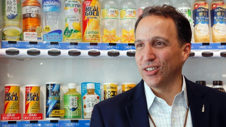 In this Tuesday, Nov. 22, 2016 photo, Raymond Shelton, senior executive officer at the Coca-Cola East Japan, stands before a vending machine with his company's beverages sold in Japan, none of which is Coke, but rather various teas, coffee, water and juices, at Coca-Cola East Japan headquarters in Tokyo Nov. 22, 2016. Coca-Cola has been the No. 1 beverage maker in Japan for half a century, but it's not thanks to the popularity of Coke. Instead, the American soft-drink brand has adapted to the quirky ways this society quenches its thirst. Shelton, senior executive officer for Coca-Cola East Japan, says he has never seen such innovation or variety as he has in Japan.  (AP Photo/Yuri Kageyama)