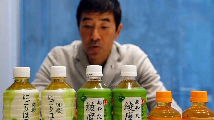 "In this Nov. 9, 2016 photo, Takashi Wasa, senior vice president at Coca-Cola Japan, shows the company's green tea beverages ""Ayataka"" at Tokyo headquarters during an interview. Coca-Cola has been the No. 1 beverage maker in Japan for half a century, but it's not thanks to the popularity of Coke. Instead, the American soft-drink brand has adapted to the quirky ways this society quenches its thirst. Among 20 Coca-Cola global brands that bring in $1 billion or more in annual sales, four were developed in Japan: the Georgia coffee lineup; Aquarius, a Gatorade-like drink; I Lohas bottled water and Ayataka green tea. (AP Photo/Yuri Kageyama)"