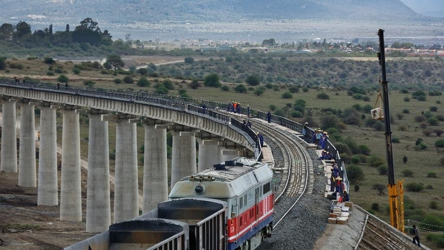 In this photo taken Wednesday, Nov. 23, 2016, a train returns from transporting ballast used in the construction of the Nairobi-Mombasa railway, and passes over an existing bridge that goes across a corner of Nairobi National Park in Nairobi, Kenya. A controversial Chinese-built railway project involving an even larger 6km bridge that would go all the way over the beloved protected area in Kenya's capital has divided conservationists in this East African country. (AP Photo/Ben Curtis)