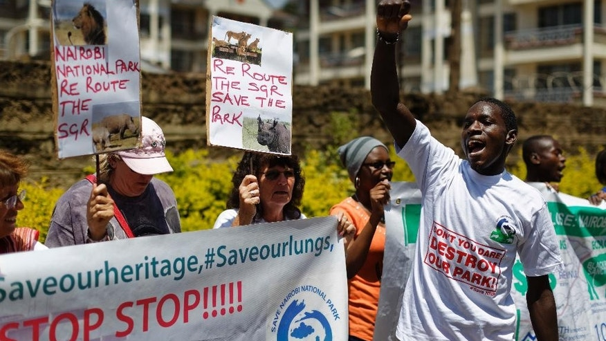 FILE - In this Monday, Oct. 17, 2016 file photo, environmental and wildlife campaigners gather to march to the Chinese embassy to protest the proposed construction of a Chinese-built railway bridge, in the capital Nairobi, Kenya. A controversial Chinese-built railway project involving a 6km bridge that would go all the way over the beloved Nairobi National Park in Kenya's capital has divided conservationists in this East African country. (AP Photo/Ben Curtis, File)