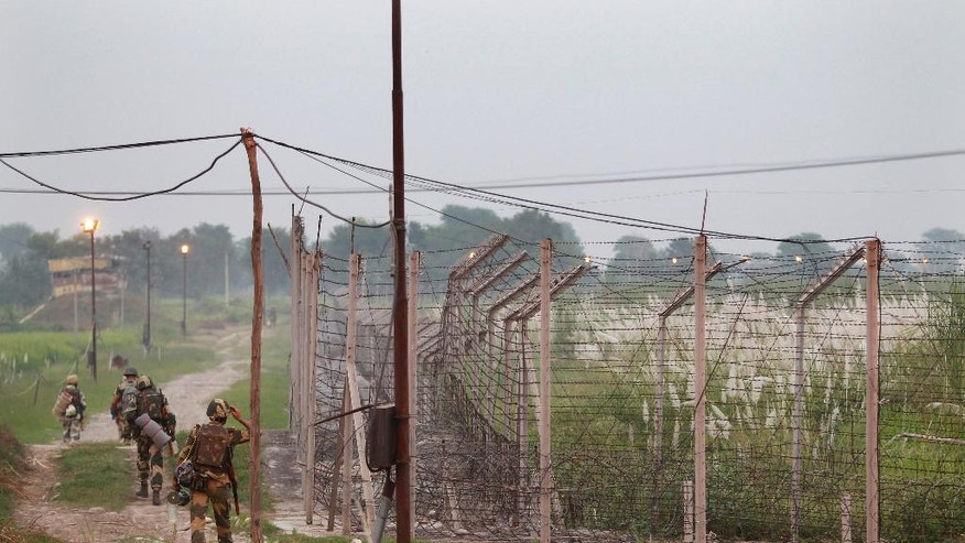 FILE - In this Oct. 1, 2016, file photo, Indian Border Security Force soldiers walk with their belongings for night duty near the India-Pakistan international border area at Gakhrial boder post in Akhnoor sector, about 48 kilometers (30 miles) from Jammu, India. An uneasy calm has fallen over the de facto border between the Indian and Pakistani-controlled portions of Kashmir after months of deadly firing and signs that the two countries were engaged in a brinkmanship not seen for decades. Though guns have gone silent for the past five days, analysts say the two nuclear-armed neighbors have displayed unprecedented aggression this year without pursuing any real lines of diplomacy. (AP Photo/Channi Anand, File)