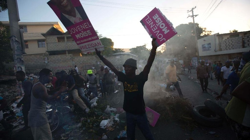 A supporter of presidential candidate Maryse Narcisse, from Fanmi Lavalas political party, holds up campaign posters of rival candidate Jovenel Moise, from PHTK party, at a road block in Port-au-Prince, Haiti, Monday Nov. 28, 2016. Before results have been announced, supporters of Narcisse assert their candidate has won, and that only electoral fraud would keep her from office. (AP Photo/Dieu Nalio Chery)