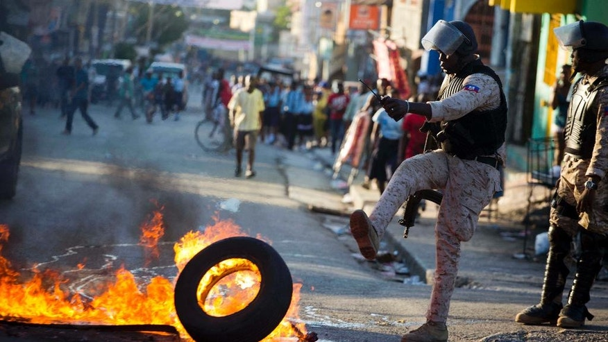 A national police officer removes a tire set fire by supporters of presidential candidate Maryse Narcisse, from Fanmi Lavalas political party, in Port-au-Prince, Haiti, Monday, Nov. 28, 2016. Before election results have been announced, supporters of Narcisse assert their candidate has won, and that only electoral fraud would keep her from office. (AP Photo/Dieu Nalio Chery)