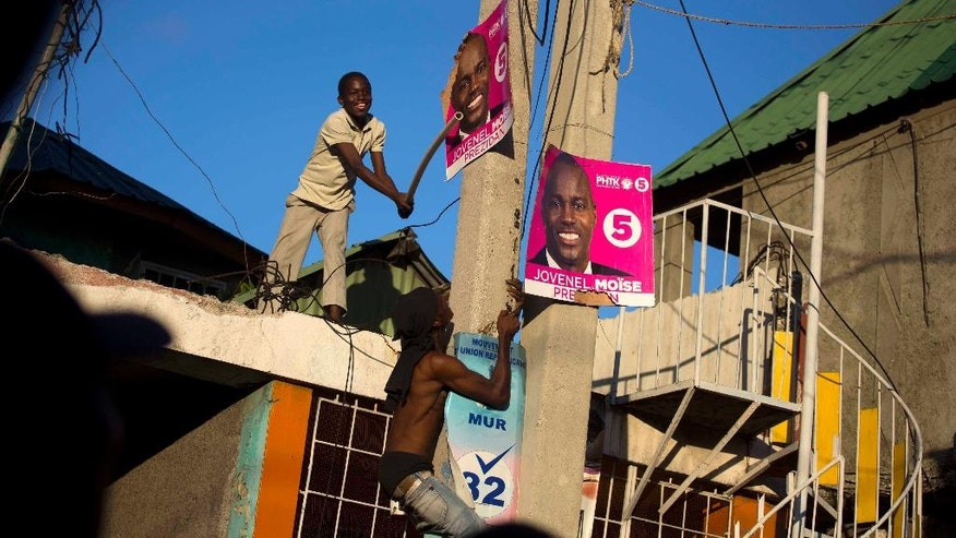Supporters of presidential candidate Maryse Narcisse, from the Fanmi Lavalas political party, take down campaign posters of rival candidate Jovenel Moise, from PHTK party, during a protest in Port-au-Prince, Haiti, Monday, Nov. 28, 2016. Before results have been announced, supporters of Narcisse assert their candidate has won, and that only electoral fraud would keep her from office. (AP Photo/Dieu Nalio Chery)